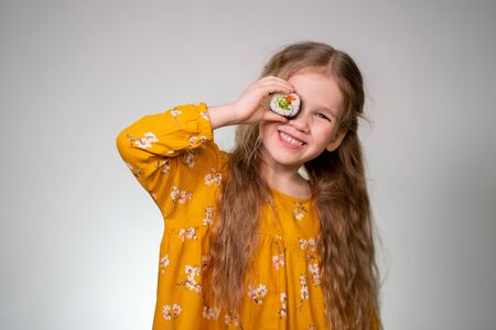The Girl holding rolls have a face like binoculars. Japanese cuisine home delivery. On a white background in an orange dress. Long curly hair. It is ridiculous and stupid.
