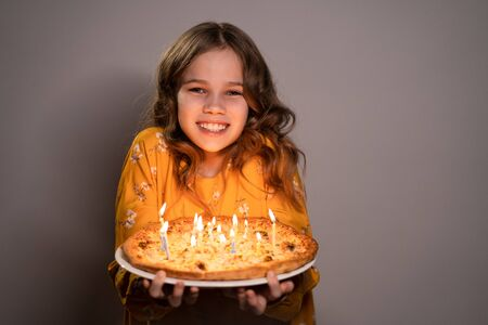 a teen blonde girl holding a pizza with candles is smiling on a white background. Original birthday.