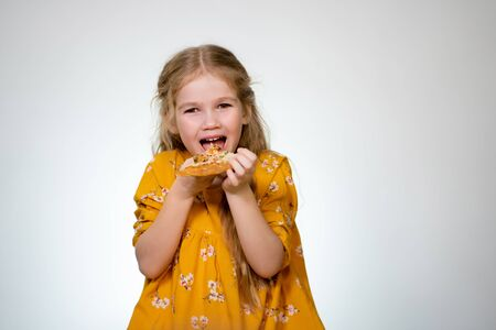 Happy Birthday. The Little girl blonde laughing and chewing on a delicious piece of pizza on white background