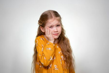 Strong Toothache a little girl with long blond hair in a yellow dress. Posing on a white background. Archivio Fotografico