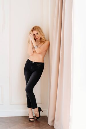 a beautiful slender blonde girl topless in black trousers with heels stands in a white room