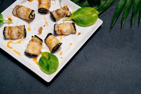 Rolls eggplant appetizer in a white plate on a black table