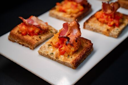toast with vegetables and bacon in a white plate on a black background. close up