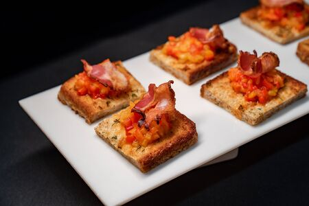 toast with vegetables and bacon in a white plate on a black background.