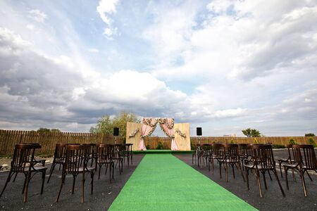 decor of the outdoor wedding ceremony area without people . waiting for guests and the bride and groom. Standard-Bild