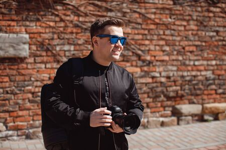 portrait A male photographer in black clothes and sunglasses with a camera in his hands smiles
