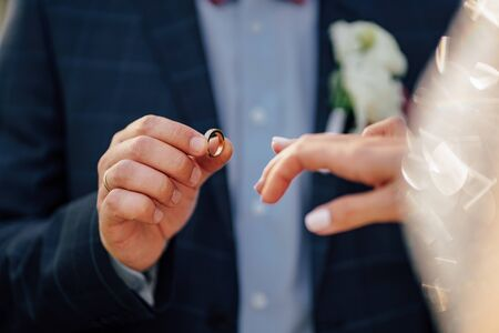 the bride and groom put on each other rings. close-up. wedding traditions.