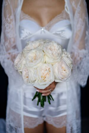 morning bride in her underwear holding a bouquet. without a face.