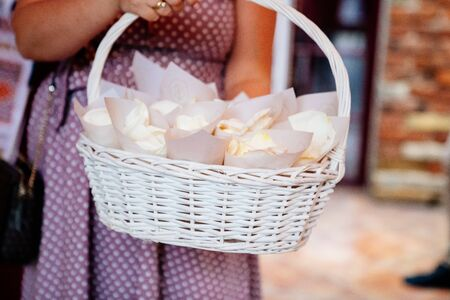 rose petals in the envelopes for the guests in a white basket. showered the newlyweds. wedding.