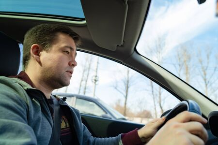 man in the grey sweater behind the wheel of the car rides and looks forward Stock fotó