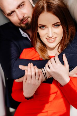 man in suit and woman in red dress hugging each other. closeup portrait. Archivio Fotografico