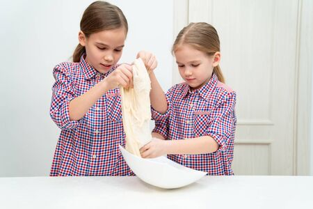 the children kneaded the dough themselves on white table for pizza or pie. cook at home.