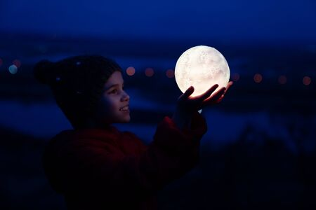 teenager girl in a cap and a red jacket holds a full glowing moon Stock Photo