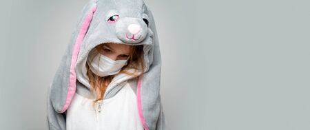 teen girl in kigurumi rabbit in a medical mask at home in quarantine. close up. copy space. lower head