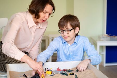 the boy with the teacher with glasses is sand therapy on the table with light.