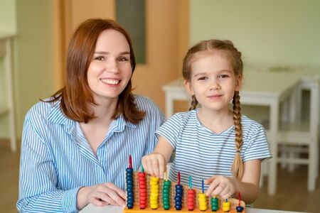 mom with a girl learning to add and subtract with mixed accounts. educational classes for children.