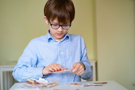 boy playing table learning game design and assemble face