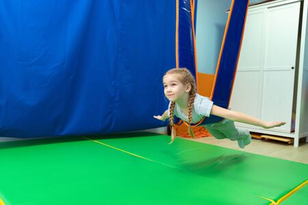 a little girl in hammock made of elastic material. to replenish sensory experience, enhance tactile and muscular sensitivity, improve coordination and orientation in space