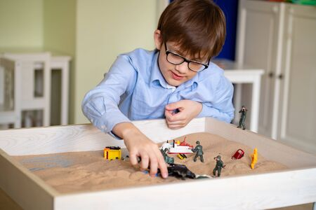 the boy with glasses is sand therapy on the table with light.