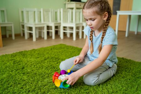 little girl playing with a whirligig colourful musical bells. sessions with children.