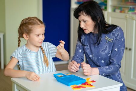 teacher and the little girl solve the mathematical puzzle in the kindergarten class. Stock fotó