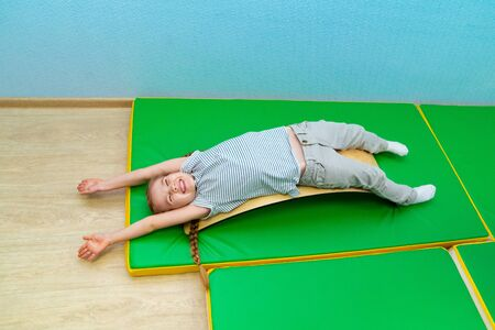 a little girl is lying on her back on a touch integration Board