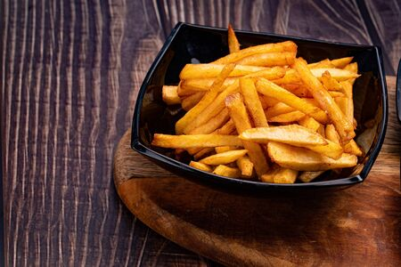 a potatoes fries in a black dish close-up. wooden Board.