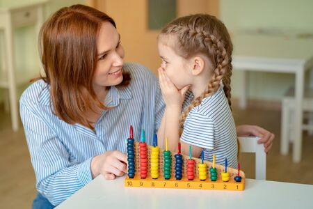mom with daughter learning to add and subtract with mixed accounts. educational classes for children.