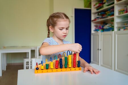 small girl learning to add and subtract with mixed accounts. educational classes for children.