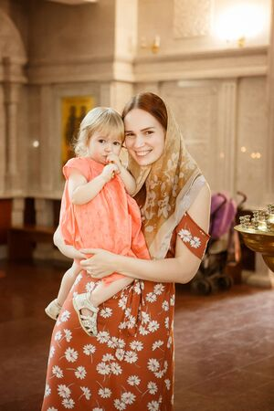 mom in a scarf on the head and daughter in the Church. religion in the family and for children. Orthodox Cathedral.