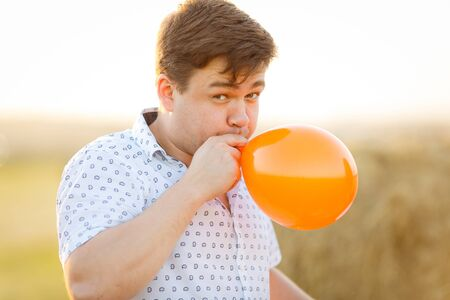 male dad inflates an orange balloon in a field at sunset