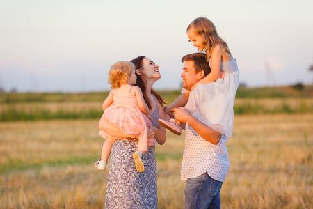 family with two daughters plays at sunset on the sloping field. walks in the countryside and rural areas. dad ride the kid on shoulders Stock fotó