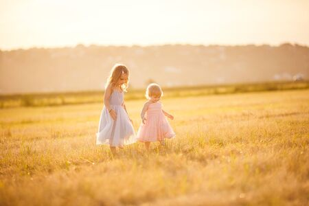 two little girls going together on the sloping wheat field at sunset in village Foto de archivo