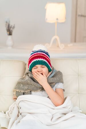 the little girl in the hat, the scarf and blanket yawns sitting on the couch and it hurts, she is sick, she is cold.