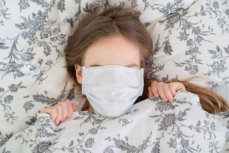 portrait of teen girl lying in bed in a medical mask in the quarantine.