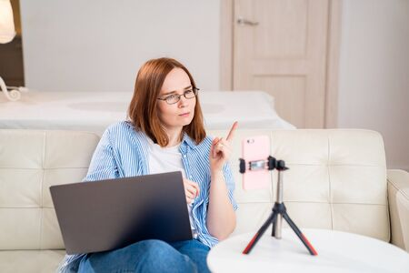 blogger or teacher, the woman teaches, conducts live, record the webinar, communicating online via the phone. the social distance. stay home. epidemic and quarantine.
