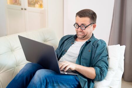 funny freak with glasses, blogger, freelancer, businessman working online lying on the couch. social distance. epidemic and quarantine. stay home.