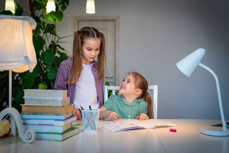 older sister helps the younger children with their lessons, writings and preparation for school. isolation and social distance. quarantine and epidemic.