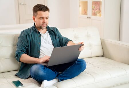 businessman, freelancer, blogger working online sitting on the couch. social distance. stay home. epidemic and quarantine.