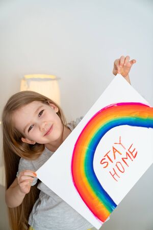 child girl with blond hair drew a rainbow and a poster stay home. flashmob chasetherainbow. 写真素材