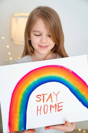 a small girl with blond hair drew a rainbow and a poster stay home. flashmob chasetherainbow.