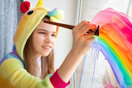 brush. teen girl in kigurumi unicorn draws the rainbow on the window. flashmob chasetherainbow. stay home.