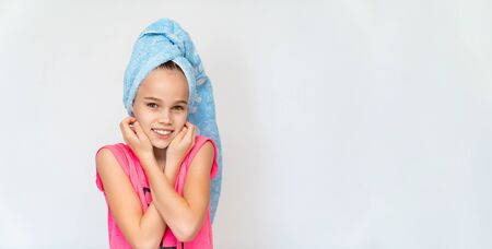 cheerful girl in a blue towel and a pink t-shirt after taking a bath. hygiene and hair washing. copy space.