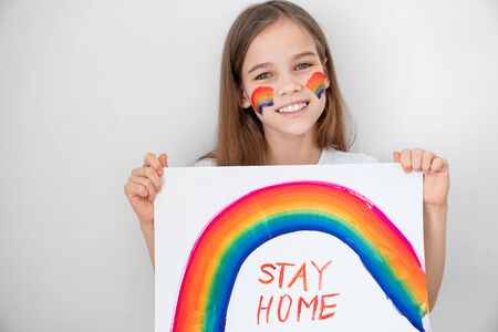 teen girl with blond hair drew a rainbow and a poster stay home. flashmob chasetherainbow. 写真素材