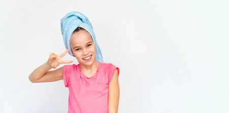 smiling girl in a blue towel and a pink t-shirt after taking a bath. hygiene and hair washing. copy space.