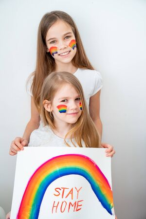 beautiful two kid girls with blond hair drew a rainbow and a poster stay home. flashmob chasetherainbow. 写真素材