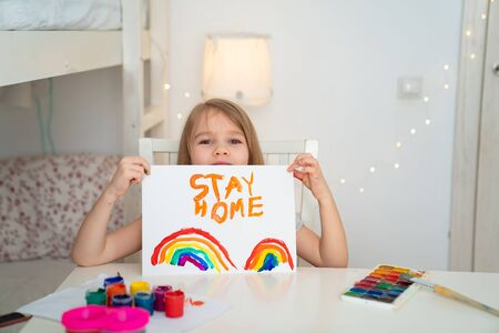 little girl with blond hair drew a rainbow and a poster stay home. flashmob chasetherainbow. 写真素材