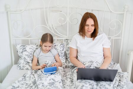 stay home. little girl daughter and mom freelancer play on the computer in the bedroom