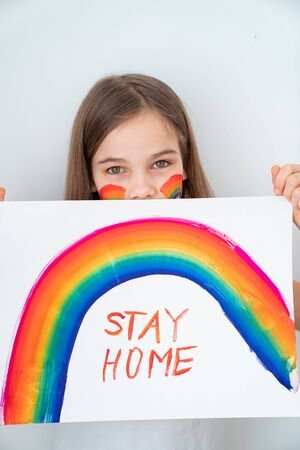 stay home. teen girl with blond hair drew a rainbow and a poster. flashmob chasetherainbow.