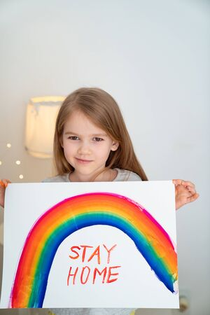 child with blond hair drew a rainbow and a poster stay home. flashmob chasetherainbow. 写真素材